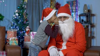 Cute Indian boy whispering his wishes in Santa's ear during Christmas time in India