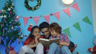 Happy Indian father reading a storybook to his cute little children on Christmas holiday