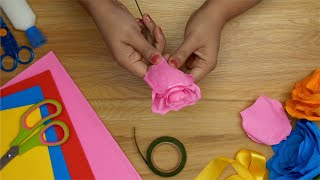 Top view of making an artificial flower using scissors, tape and glue