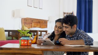 Happy Indian married couple making online payments on their tab using bank credit and debit cards
