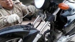 Bombeiro capturando filhote de jiboia em guidão de moto em Mato Grosso Do Sul