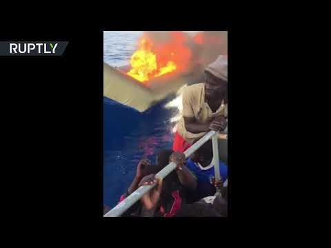 RAW: Migrant boat set on fire by Libyan coastguard in Mediterranean