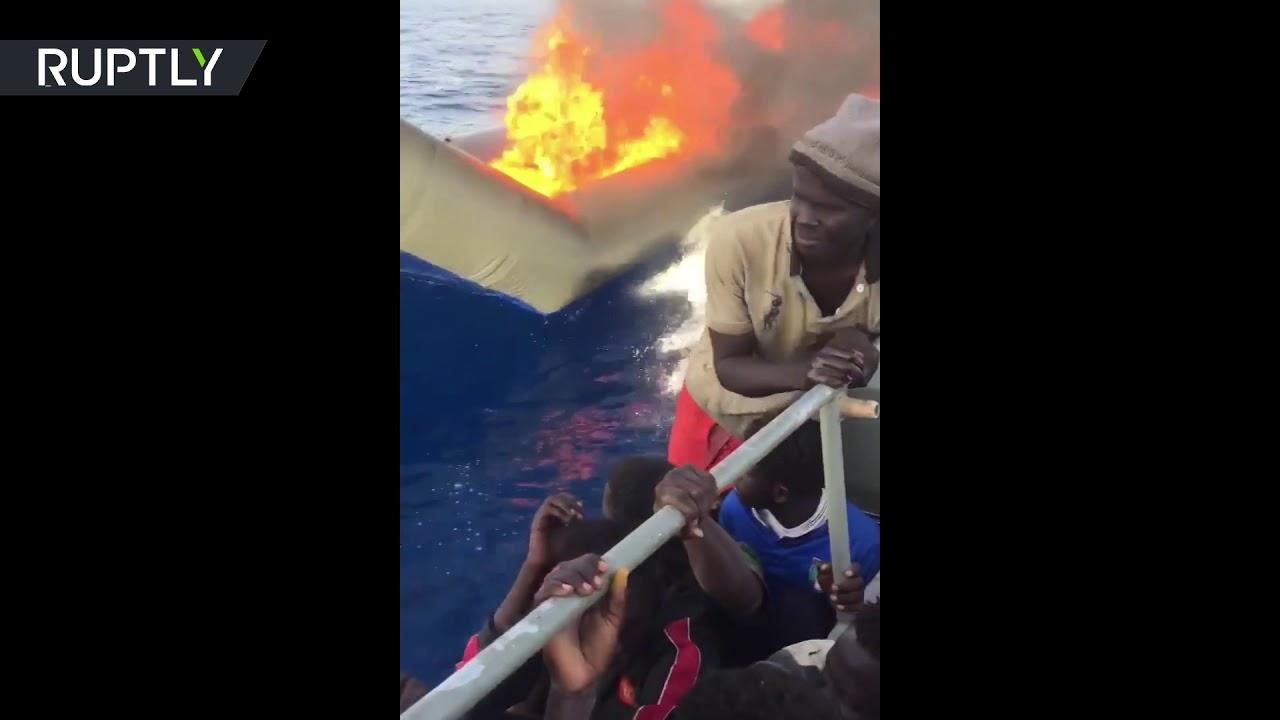 RAW: Migrant boat set on fire by Libyan coastguard in Mediterranean