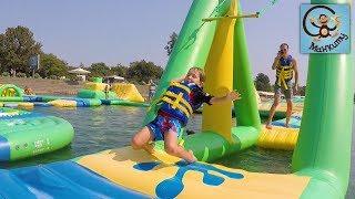 Парк аттракционов на воде, необычный аквапарк. Дети на полосе препятствий. МанкиТайм