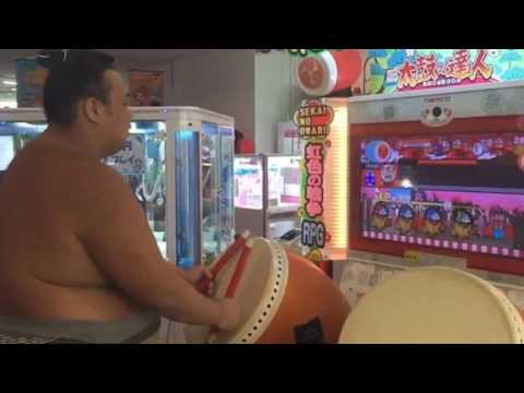 Sumo wrestler shows off his amazing musical skills as he expertly plays an arcade video game