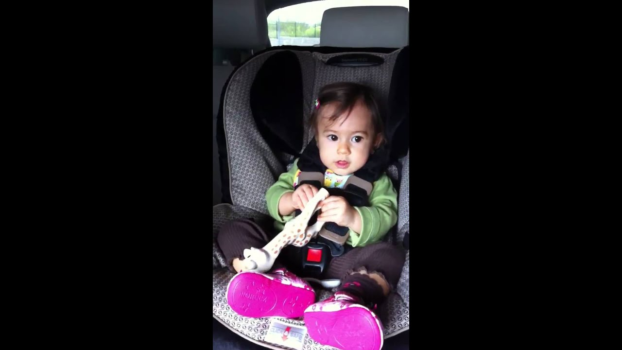 little girl in car seat dancing