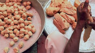 Close up shot of a dark complexioned man's hands making dough balls in large quantity for a function
