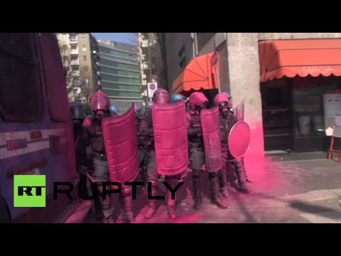 Riot police painted pink during clashes with anti-government protesters in Italy