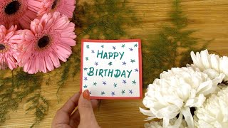 Woman hands placing a card with 'Happy Birthday' text on a decorated wooden table