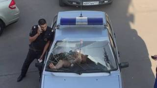 A woman breaks a police car windshield with her bare feet!