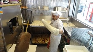 Master Baker Gino making Turkish Flat Bread Pide (Ekme i) in a wood fired oven at Crystal, London