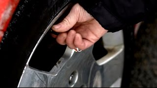 Close-up of person checking tire pressure