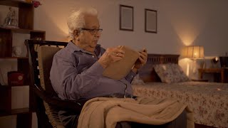 Shot of a retired Indian man reading a book sitting on a rocking chair