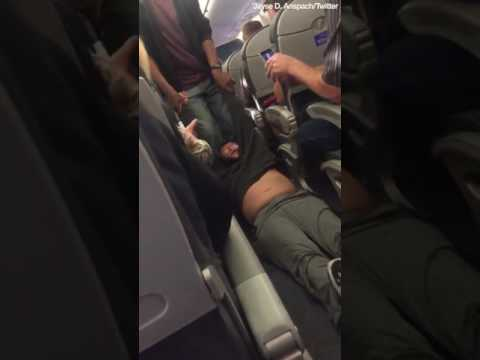 Bleeding UA passenger dragged off overbooked flight after refusing to give seat to airline staff