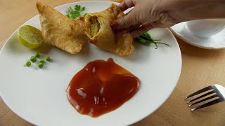 Woman's hand dipping crispy samosa into tomato ketchup while having masala chai(tea)