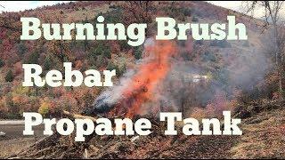 propane-tank-solar-panel-anchor-rebar-and-burning-brush