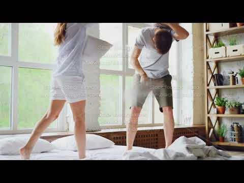 Happy couple husband and wife are having pillow fight on double bed, they are having fun smiling and
