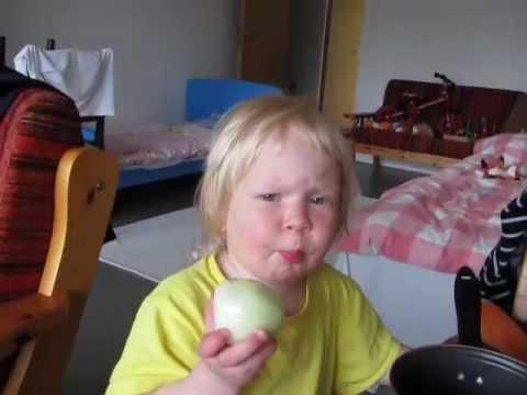 0 Garotinha comendo uma cebola crua