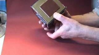 A metallic-looking puzzle box, with a sliding panel on each side.