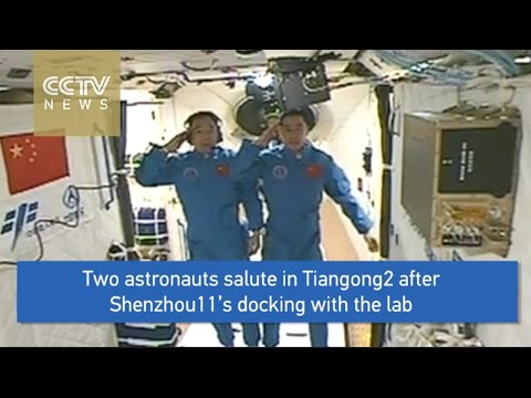 Two astronauts salute in Tiangong2 after  Shenzhou11's docking with the lab