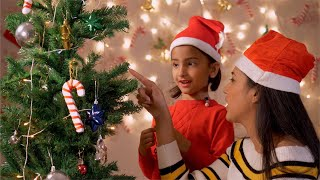 Young mother helping her daughter to decorate Christmas tree