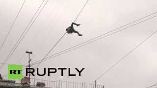 Russia: Daredevil climbs across St. Petersburg street hanging onto telephone wire