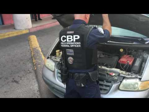 Customs officers inspect vehicles at a Nogales port of entry