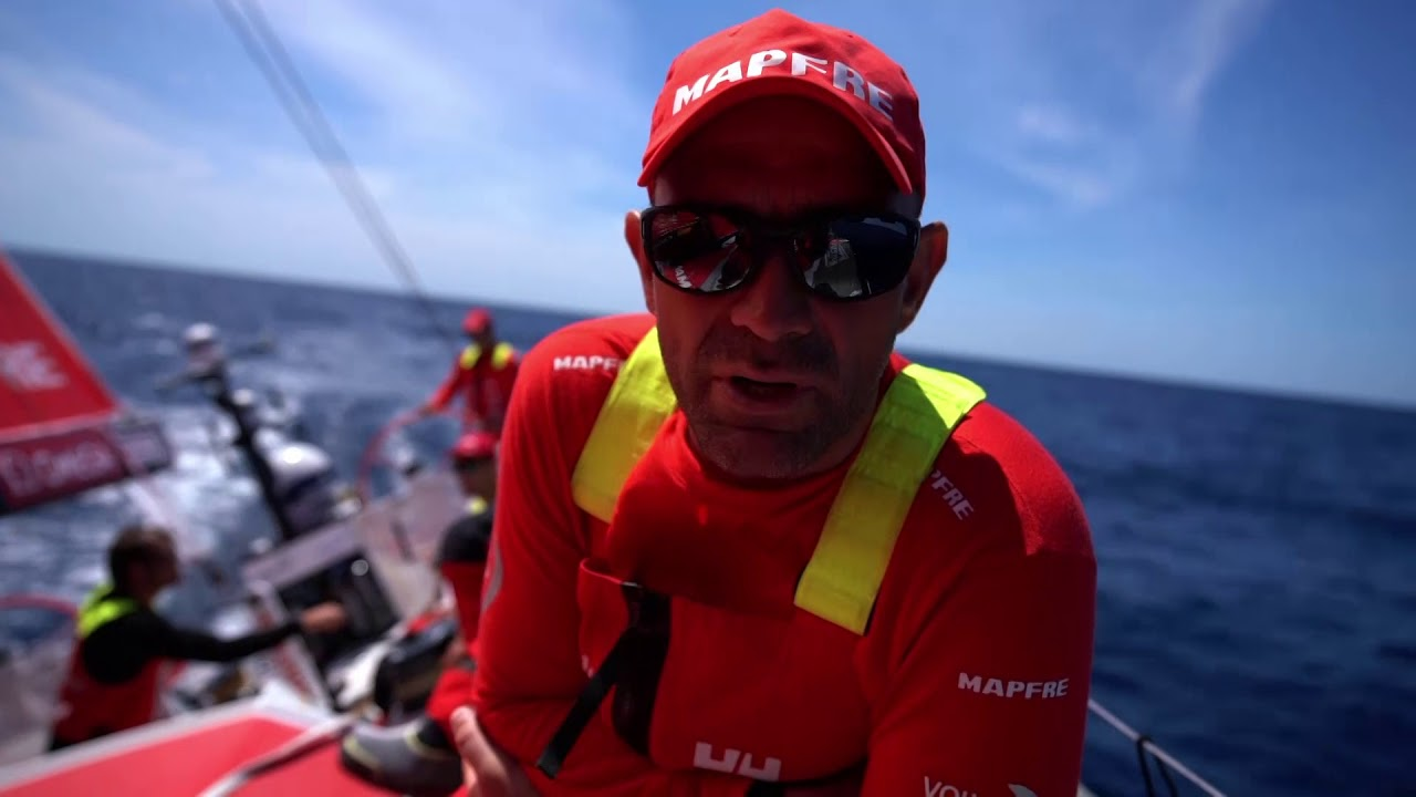 Xabi summarizes the first 2 days of the leg in Spanish. Discusses the complicated conditions, the relative positions of the northern and southern groups. Tamara, on the bow as they flop, talks in Spanish. Xabi repeats his summary in English. First time they've seen such a big split in the race. Very slow for them and Dongfeng and TTToP. The fleet in the south always kept in front of the front. They have a lot of work to do now to get to the north. They look quite strong. We need to wait and see. Tamara repeats her comments in English: In a transition. Hard to wait for the wind. Hope they'll be sailing fast soon. Xabi trims. Sophie and Blair grind. Stacking forward. Flopping. Xabi rubs his head. Instruments show them doing 3 knots. Drone shot of them floopping from above the masthead, then low and alongside in very flat water.
