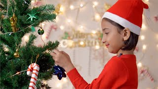 A sweet little girl in a red Santa hat is decorating a Christmas tree