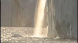 """ノルウェーの北極圏にあるスバールバル諸島。50キロにわたって氷河の絶壁を流れ落ちる大瀑布""""ブルーフォール""""は、白夜の太陽が最も低くなる深夜0時、地平線から陽の ..."""