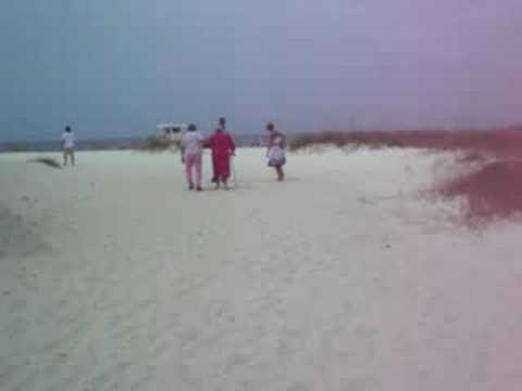 Old Lady Walking With A Cane On The Beach
