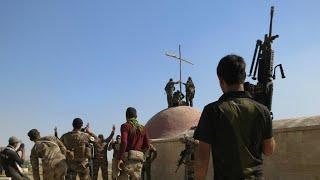 مقاتلون عراقيون يرفعون الصليب على كنيسة بعد استعادتها من الجهاديين