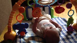 Three month old baby batting at Toys