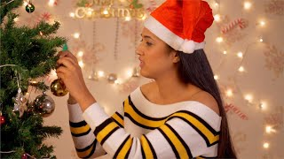 Beautiful young woman / female decorating Christmas tree