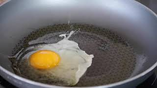 Cracking an egg into a hot pan in slow motion Fre...