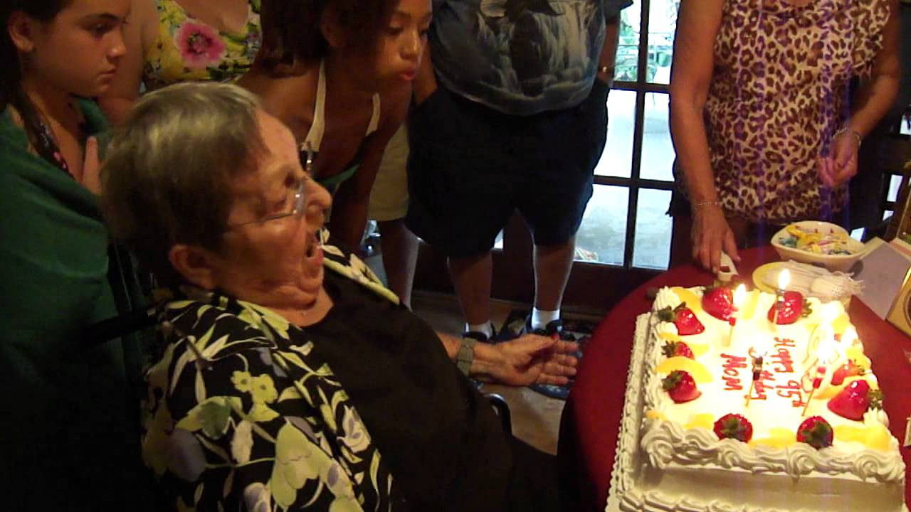 Happy 95th Birthday Grandma blowing out the candles on her cake