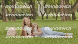 Attractive young girl student with a smartphone lies on a grass park. Rest during study