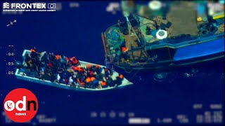 People smugglers are caught in the act on camera middle of mediterranean. they take 80 migrants board a fishing trawler towing wooden dingy b...