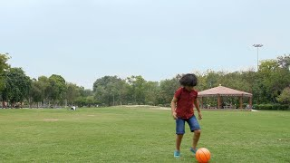 Cute Indian kid enjoying playing football in a park in casual clothing - happy childhood