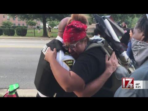 Woman hugs officer