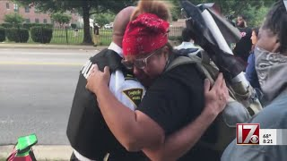 Woman hugs officer after Fayetteville police kneel in support of protests