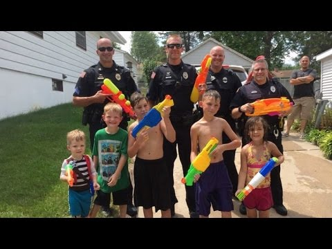 Police Officers Get Soaked In Water Gun Fight With Kids On Hot Summer Day