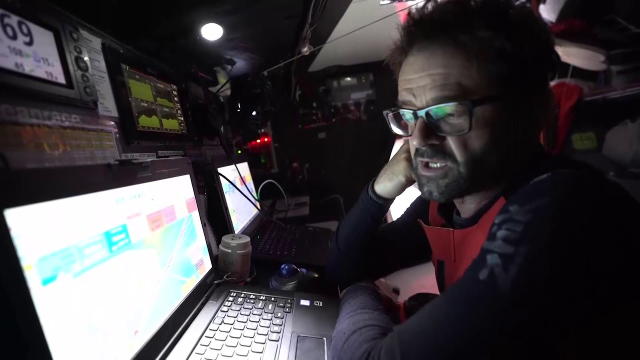 Charles, below, talks about getting the wind, finally. But less than forecast, so they lost a lot to the fleet to the south. Now they're in a better position, though, for the next 6 hours, and the 6 hours after that. Fleet could join again. Pascal at nav station: 2 or 3 days everybody is going to arrive quite at the same time at the corner of the exclusion zone. 35 knots of wind with close reaching coming up. Charles: Next 24 hours are going to be very complicated to manage. Lots of wind. Not possible to always have the good sail; have to manage, to be smart, to always make the good call.