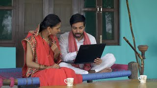 Young educated villager teaching basic usage of computer to his wife - village lifestyle