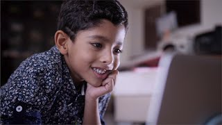 A young Indian kid watching a movie on the laptop, laughing and talking to himself - Tech impact on kids