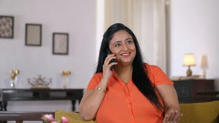 Indian woman talking on the cell phone while sitting on a couch at home - Technology concept
