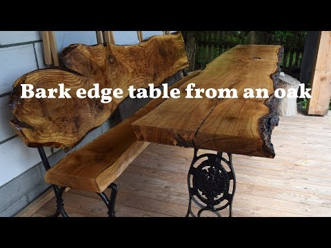 Wooden live edge table from big piece of an oak  - long, natural bark and black metal