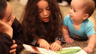 Cousins reading their baby cousin The Very Hungry Caterpillar