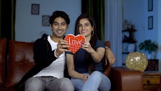 Smiling young couple showing a red heart to the camera on Valentine's day in India