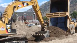 CAT dump truck dumping dirt while a 366E Excavator cleans up the pile